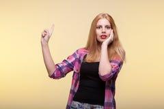 Zdziwiona kobieta wskazuje up z jeden i trzyma jej twarz wręcza obrazy stock