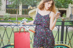 Zdziwiona kobieta z pluskwami używać telefon komórkowego blisko rocznika bicyklu Obraz Stock