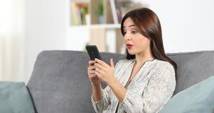 Zdziwiona kobiety czytania telefonu zawartość w domu zbiory wideo