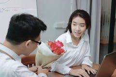 Zdziwiona młoda Azjatycka biznesowa kobieta excited dostawać bukiet czerwieni róża w biurze na valentine ` s dniu Miłość i romans Zdjęcie Royalty Free