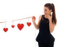 Zdziwiona młoda brunetki kobieta z czerwonym sercem w ręk pozować odizolowywam na białym tle Świątobliwy walentynki ` s dzień Obraz Stock