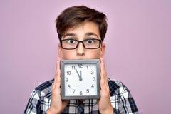 Zdziwiona młoda chłopiec z zegarem obraz royalty free