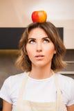 Zdziwiona młoda dama z jabłkiem na jej głowie Obraz Stock