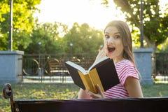 Zdziwiona młoda dziewczyna czyta książkowego outside zdjęcie royalty free