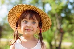 Zdziwiona mała dziewczynka w słomianym kapeluszu obrazy royalty free