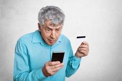 Zdziwiona stara samiec z popielatym włosy gapi się przy mądrze telefonem, może rozumieć coś, trzyma kartę, ` t, komórkową i kredy zdjęcie royalty free