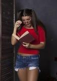 Zdziwiona studencka dziewczyna czyta książkę młoda kobieta w czerwonym wierzchołku i drelichu zwiera z szkłami Zdjęcia Stock