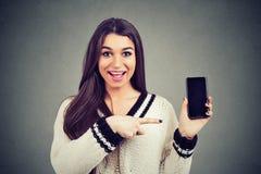 Zdziwiona szczęśliwa kobieta w pulowerze pokazuje wskazywać przy pustym smartphone ekranem zdjęcie stock