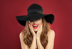 Zdziwiona wzorcowa kobieta w czarnym kapeluszu na czerwonym tło portrecie zdjęcie stock
