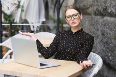 Zdziwione biznesowe kobiety jest ubranym szkła, czarna koszula w kawiarni Obrazy Stock