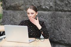 Zdziwione kobiety jest ubranym czarną koszula w kawiarni patrzeje w laptop Fotografia Royalty Free