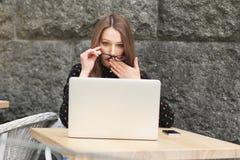 Zdziwione kobiety jest ubranym szkła, czarna koszula w kawiarni patrzeje w laptop Fotografia Royalty Free