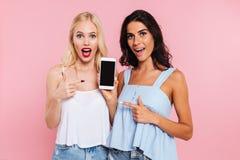 Zdziwione uśmiechnięte damy pokazuje pustego ekran odizolowywającego smartphone fotografia royalty free