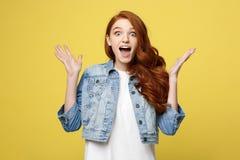 Zdziwionego czerwonego włosianego nastoletniej dziewczyny przedstawienia szokujący wyrażenie z coś Odizolowywający na jaskrawym ż zdjęcia royalty free