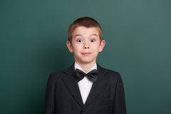 Zdziwionego szkolnej chłopiec portreta chalkboard pobliski zielony pusty tło, ubierający w klasycznym czarnym kostiumu, jeden ucz Zdjęcia Stock