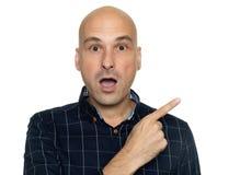 Zdziwiony łysy mężczyzna wskazuje palec kopiować przestrzeń zdjęcia royalty free