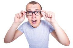 Zdziwiony śmieszny młody człowiek w szkłach z brasami na zębu isolat obrazy stock