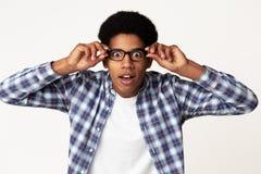 Zdziwiony afroamerykański studencki wzruszający szkieł czuć szokuję obrazy stock