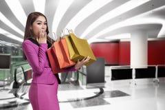 Zdziwiony azjatykci biznesowej kobiety mienie w ona ręki dużo zakupy Obrazy Royalty Free
