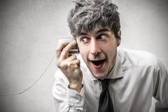 Zdziwiony biznesmen próbuje słuchać coś Obrazy Stock