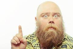 Zdziwiony brodaty mężczyzna wskazuje up Obrazy Stock