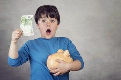Zdziwiony dziecka oszczędzania pieniądze w prosiątko banku Obraz Stock
