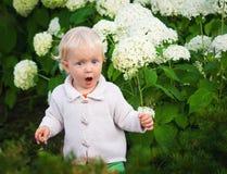 Zdziwiony dziecko wśród kwiatów Obrazy Royalty Free