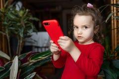 Zdziwiony dziecko z smartphone ubierał w czerwieni inside w domu Obrazy Stock