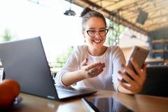 Zdziwiony freelancer mieszał biegowych kobiet spojrzenia przy smartphone i no może wierzyć jej wygrywał loteryjną nagrodę Pomyśln obraz royalty free