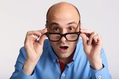 Zdziwiony mężczyzna patrzeje kamerę w eyeglasses obraz royalty free