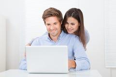 Zdziwiony mężczyzna patrzeje kobiety podczas gdy używać laptop zdjęcia stock