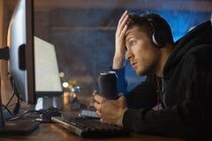 Zdziwiony mężczyzna pracuje z komputerem przy nocą Fotografia Royalty Free