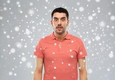 Zdziwiony mężczyzna w polo koszulce nad śnieżnym tłem zdjęcia royalty free