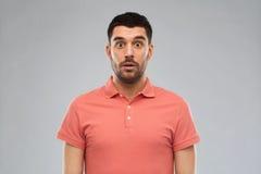 Zdziwiony mężczyzna w polo koszulce nad szarym tłem zdjęcia stock