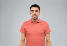 Zdziwiony mężczyzna w polo koszulce nad szarym tłem zdjęcie stock