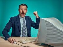 Zdziwiony młody człowiek Pracuje Na komputerze Przy biurkiem zdjęcie royalty free