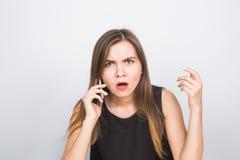 Zdziwiony młody bizneswoman opowiada na telefonie komórkowym Obrazy Royalty Free