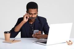 Zdziwiony murzyn trzyma telefon komórkowego, czyta wiadomość tekstową z zdziwieniem, spojrzenia przez widowisk, robi rejestrom w  obraz stock