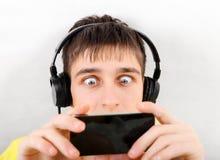 Zdziwiony nastolatek z telefonem komórkowym zdjęcie stock
