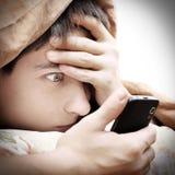 Zdziwiony nastolatek z telefonem komórkowym zdjęcie royalty free