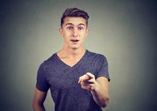Zdziwiony przystojny młody człowiek wskazuje palec przy kamerą zdjęcie stock