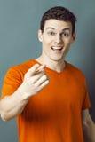 Zdziwiony uśmiechnięty sporty mężczyzna pokazuje coś z wskaźnikiem Fotografia Royalty Free