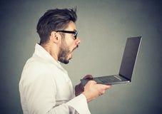 Zdziwiony zadziwiający mężczyzna z laptopem zdjęcie royalty free