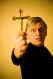 Zealous Christian. A preaching avid man holding a golden cross Royalty Free Stock Image