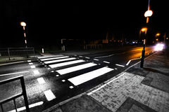 Zebra crossing. At night with car approaching. Road safety awareness royalty free stock image