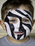 Zebra face paint. On young boy stock photography