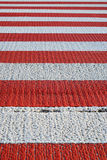 Zebra of the pedestrian crossing, close-up. Red and white striped marking of pedestrian crossing Royalty Free Stock Photo