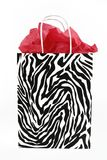 Zebra print gift bag. Zebra print gift bag with red tissue paper inside, against a white background Royalty Free Stock Images