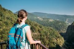 Zeda-gordi, Georgia Задний взгляд женщины стоя на узкой дороге висячего моста или шкентеля до 140 метров выше Стоковое Фото