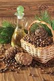 Zedernkegel, Nüsse und Zedernnussöl auf einem Holztisch Stockfoto
